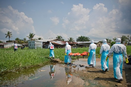 Red Cross workers remove a body for a safe and dignified burial during Ebola outbreak