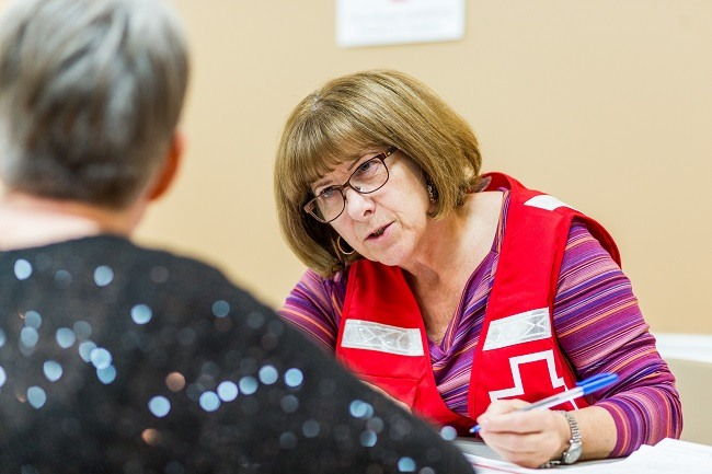 A Canadian Red Cross volunteer sits at a table and helps register someone
