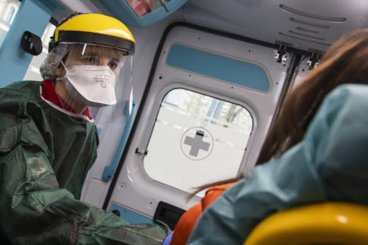 medical staff wearing PPE in the back of ambulance with patient